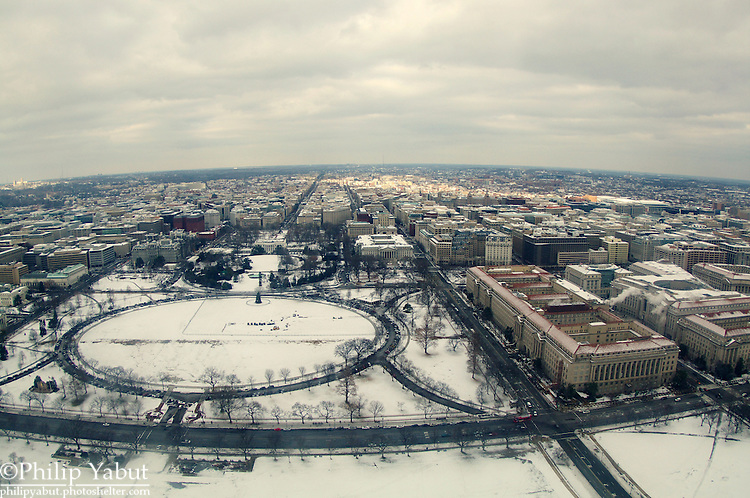 Looking north from the top of the Washington Monument, snow covers the Ellipse and the White House grounds.