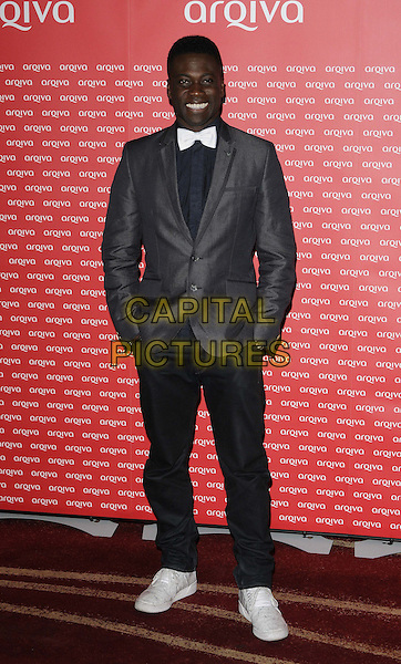 Ortis Deley.The Arqiva Commercial Radio Awards, Park Plaza Westminster Bridge Hotel, Westminster Bridge, London, England..July 4th, 2012.full length grey gray suit jacket black shirt white bow tie hands in pockets jeans denim trainers sneakers .CAP/CAN.©Can Nguyen/Capital Pictures.