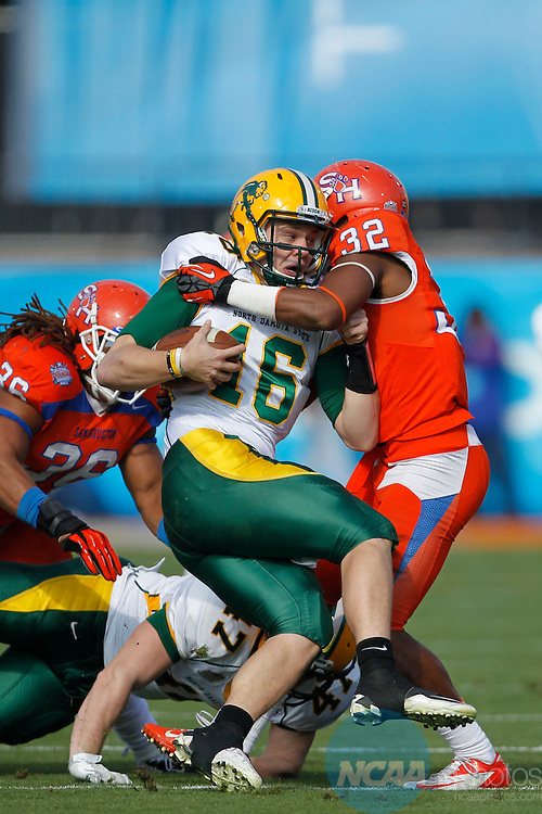 05 JAN 2013: Quarterback Brock Jensen (16) of Northa Dakota State is hit and taken down by Kenneth Jenkins (32) of the Sam Houston State Bearkats in the first half during the Division I Men's Football Championship held at FC Dallas Stadium in Frisco, TX.  North Dakota State defeated Sam Houston State 39-13 for the national championship. Ron Jenkins/NCAA Photos