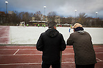 Two spectators watching the second-half at Willy-Kressmann-Stadion as Turkiyemspor Berlin (red) play BSC Rehberge in a Berlin Landesliga fixture which they won 3-0. The club was formed in 1978 to represent members of Berlin's large Turkish community and achieved several promotions and local cup wins throughout the first 15 years of their existence. Since then, financial problems have led to successive relegations and they now find themselves in the city's second division.
