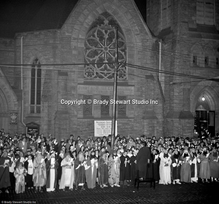 Pittsburgh PA: View of Christmas Services outside the First Luthern Church on Grant Street in Pittsburgh - 1958.  Image of Pastor leading the church choir and faithful in song and prayer.  Many of the group were dressed in period clothing at the time of Jesus's birth.
