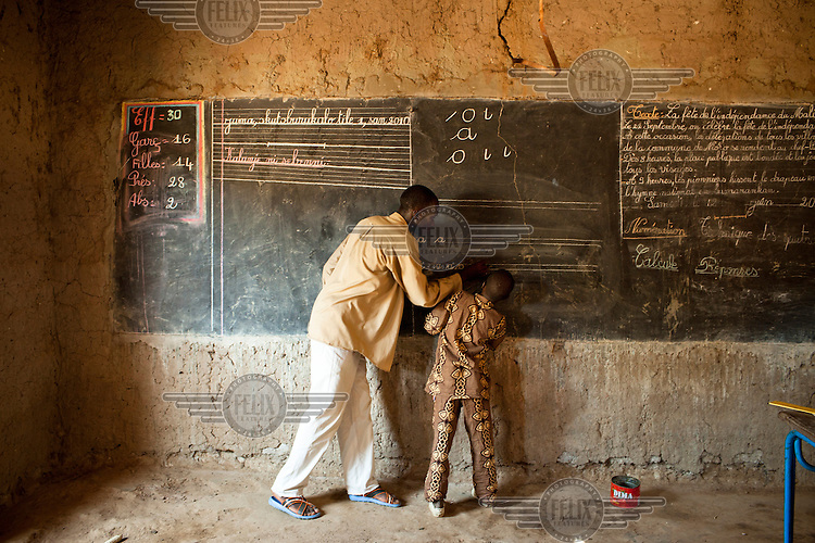 A teacher stands with one of his pupils at the blackboard writing out the alphabet at a Speed School. This offers an accelerated nine-month learning programme that equips out-of-school children with the basic education and skills needed to pass public school entrance exams and enter the formal school system. /Felix Features