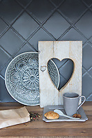 The tiles in the kitchen have been painted a signature grey and a collection of kitchen accessories is displayed on the wooden work surface