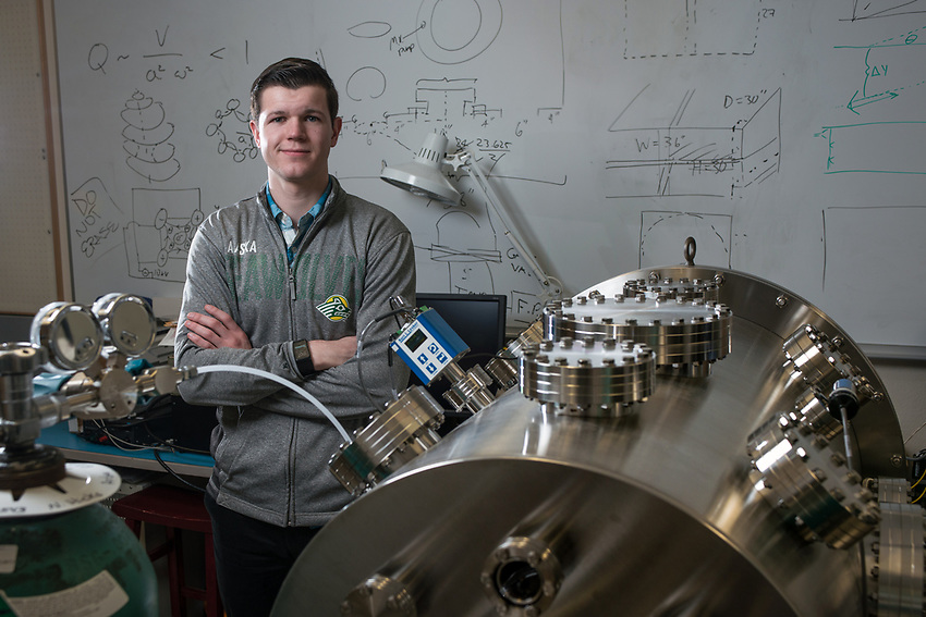 Mechanical Engineering Senior Peter Renner with an ultra-high vaccuum chamber he uses to perform plasma research in UAA's Natural Sciences Building. Renner was recently  awarded an NSF Fellowship for his work.