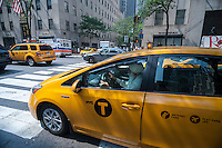 Taxis go about their business on Fifth Avenue in New York on Thursday, September 3, 2015. Because of the rise in Uber and other apps taxi medallions have decreased in worth to about $900,000 with loan delinquencies on the rise. The Melrose Credit Union has $168 million in delinquencies as of May 2015 while in January 2014 it had only $32,000. In the next six months Melrose has $212 million in maturing loans which many owners will be unable to pay.   (© Richard B. Levine)