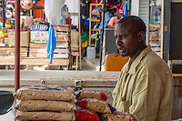 Senegal, Saint Louis.  A Shopkeeper with a Chewing Stick in his Mouth, for Cleaning Teeth.  Selling Bags of Rice.