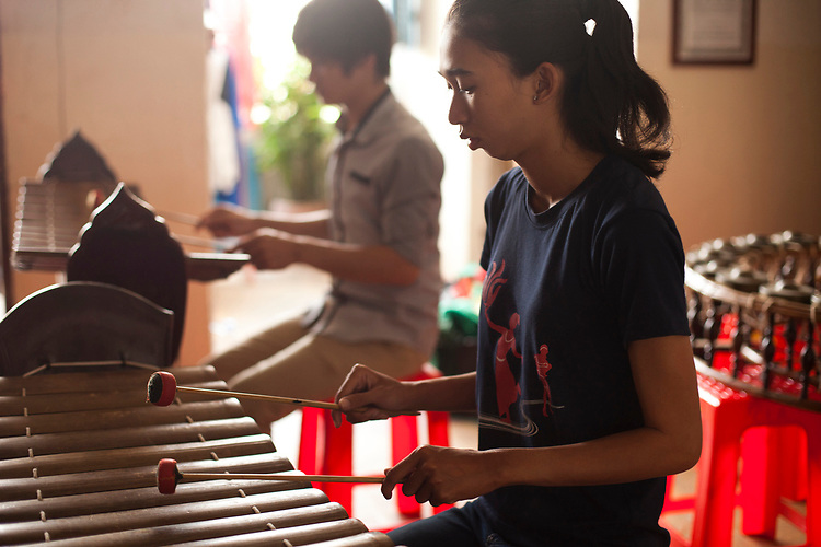A young woman practices playing a traditional Cambodian xylophone in Phnom Penh, Cambodia. <br /> <br /> Photos &copy; Dennis Drenner 2013.