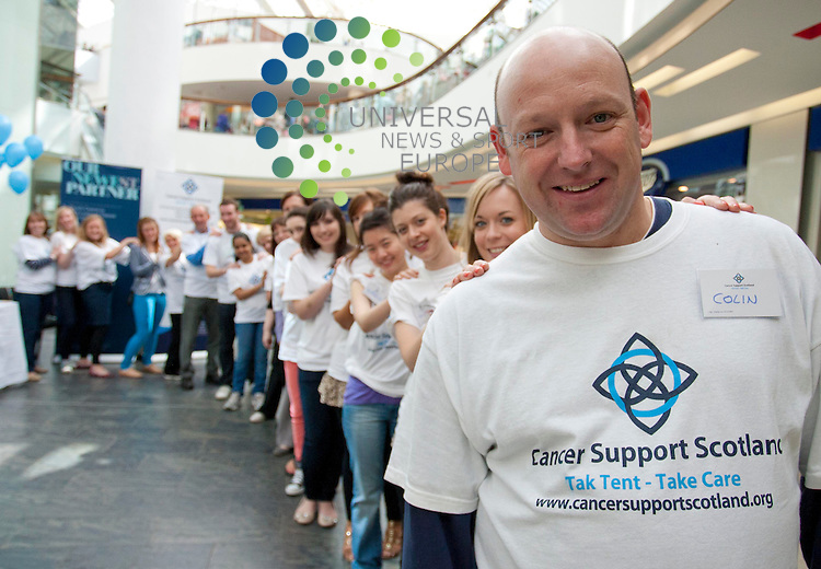 """Cancer Support Scotland charity launches Rub Shoulders To Raise Pounds campaign with """"mass """"massage"""" event. Pictured: Cancer Support Scotland volunteers create a conga line of massagers. St Enoch Centre, Glasgow. 28th July 2012. Picture: Jonathan Faulds / Universal News And Sport (Europe)"""