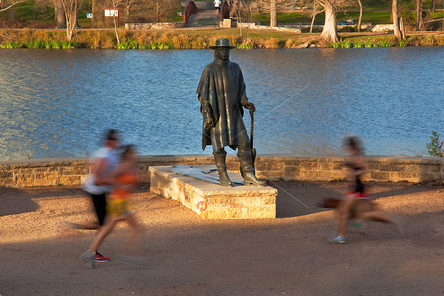 The Stevie Ray Vaughan Memorial Statue greets joggers and runners as they pass by the Lady Bird Lake Hike and Bike Trail in front of the blue waters of Lady Bird Town Lake in beautiful downtown Austin, Texas