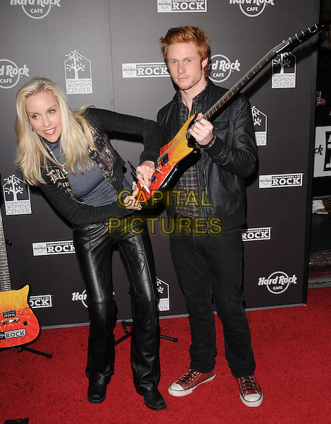 CTheRIE CURRIE of TThe Runaways & GUEST.The Hard Rock Cafe Hollywood's grand opening party in Hollywood, California, USA..October 21st, 2010.full length black grey gray jacket leather trousers guitar signing autograph .CAP/RKE/DVS.©DVS/RockinExposures/Capital Pictures.