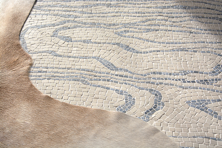 Mlima, a hand-chopped stone mosaic, shown in tumbled Travertine White and Blue Macauba. Designed by Joni Vanderslice as part of the J. Banks Collection for New Ravenna.