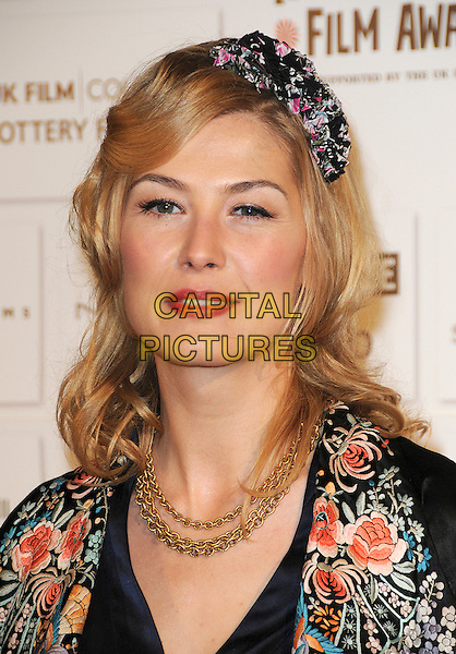 ROSAMUND PIKE .Attending The British Independent Film Awards,The Brewery, London, England, UK, December 6th 2009..arrivals portrait headshot hairband hair band floral coral peach print printed pattern gold necklace jacket navy blue  black .CAP/CAS.©Bob Cass/Capital Pictures.