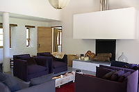 A contemporary living room with a cantilevered fireplace designed by Cyril Commarque in Le Pressoir, a 14th century mill converted into holiday lets in the grounds of the Chateau de la Bourlie in the Dordogne