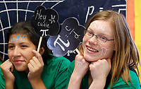 NWA Democrat-Gazette/DAVID GOTTSCHALK Guadalupe Rios (left) and Anna Bisbee, both eighth grade students at St. Vincent de Paul Catholic School, pose Wednesday, March 14, 2018, as they participate in Pi Day activities at the school in Rogers. Seventh and eighth grade students participated in five activities that featured  bracelet making, writing of Pi-Kus, and pie eating.