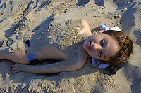 Boy buried in sand at the beach.