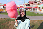 A Palestinian girl carry candy cotton at a park in Gaza city on August 18, 2019. Fayiz al-Wakeel, or 'the smile maker', developed his own candy floss machin to work by battery power to help him moving between vital districts in the Gaza city and make cotton candy with lovely shapes. Photo by Mahmoud Ajjour