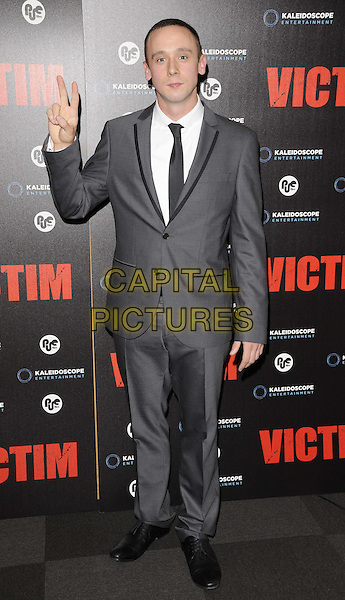 Jason Maza.The 'Victim' gala film screening, Apollo cinema, Lower Regent St., London, England..June 20th, 2012.full length white shirt grey gray suit hand waving v peace sign.CAP/CAN.©Can Nguyen/Capital Pictures.