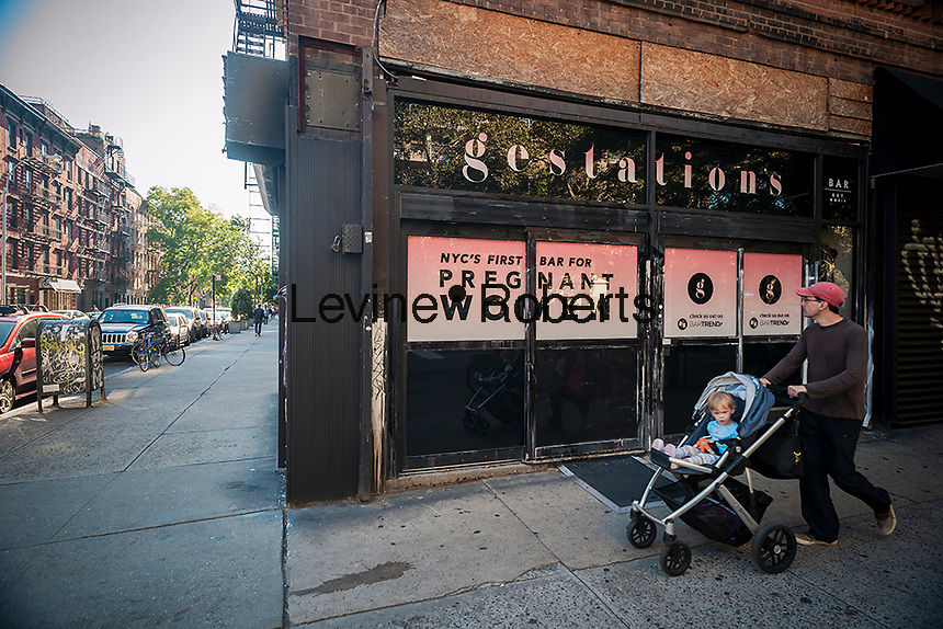 """A sign on a storefront on Saturday, September 27, 2014 in the East Village in New York heralds the imminent arrival of Gestations, NYC's first bar for pregnant women. The sign appears to be a guerrilla marketing gimmick for the app """"BARTRENDr"""" as there has been no liquor license application submitted. The bar promotes drinking for two, the bigger the belly the more you can drink, and free pregnancy kits with a pitcher of beer. (© Richard B. Levine)"""