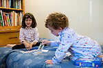 Berkeley CA  Siblings four and five playing card game together at home  MR