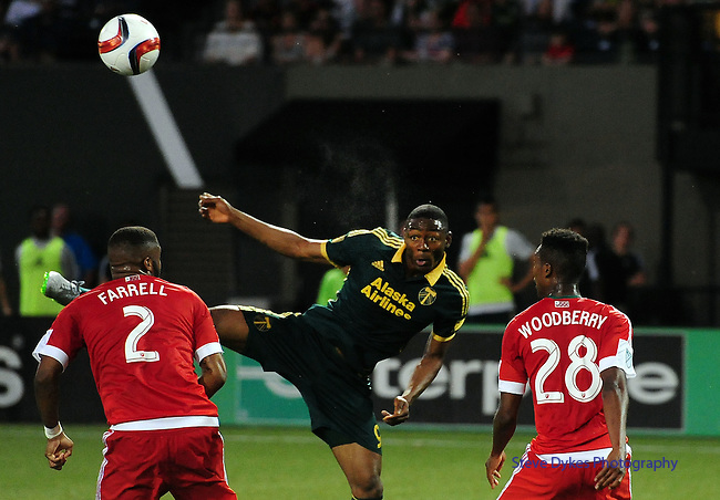 Jun 6, 2015; Portland, OR, USA; Portland Timbers forward Fanendo Adi (9) heads the ball in front of the goal as New England Revolution defender Andrew Farrell (2) and defender London Woodbury look on during the second half of the game at Providence Park. The Timbers won the game 2-0. Mandatory Credit: Steve Dykes-USA TODAY Sports