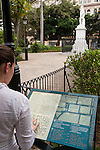 Havana, Cuba; a young woman reading a sign in braille about the white marble statue of Manuel de Cespedes which<br /> stands in the center of Parque Cespedes in the Plaza de Armas