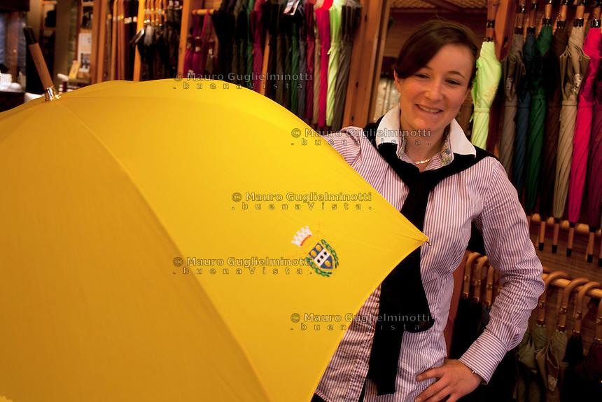 Cherbourg, gli ombrelli di Cherbourg, famosi in tutto il mondo. Una commessa in negozio, con ombrello giallo Les parapluies de Cherbourg, reconnus dans le monde entier une vendeuse dans la boutique Umbrellas of Cherbourg, famous around the world, a shop