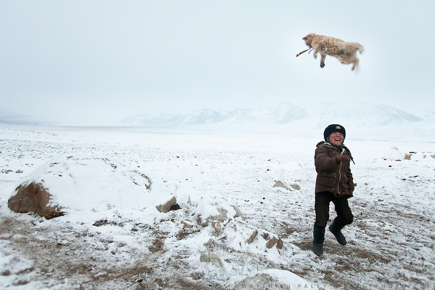 With 8 months of winter and no direct links to the outside world, the Kyrgyz face months of boredom and any possible distraction, like throwing the family cat in the air, is welcome..At the Qyzyl Qorum camp. It is the camp of the now deceased Khan (Abdul Rashid Khan, died in December 2009), and headed by the self proclaimed young Haji Roshan Khan (his son). Opium addicted Haji Roshan was never officially stated Khan and is therefore not accepted as leader by the entire Kyrgyz community. Near the Afghan-China border...Trekking through the high altitude plateau of the Little Pamir mountains, where the Afghan Kyrgyz community live all year, on the borders of China, Tajikistan and Pakistan.