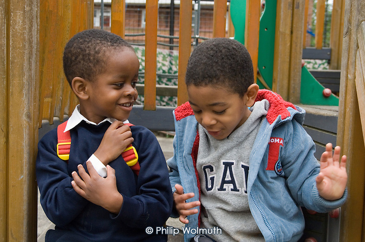 Two friends at playtime at Christ Church Bentinck Church of England Primary School, Westminster, London.