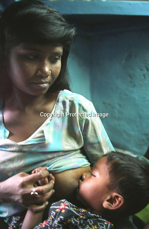 INDIA (West Bengal - Calcutta) -Khuku - Sex worker, feeds her kid at her room in Munsigaunge.- Arindam Mukherjee