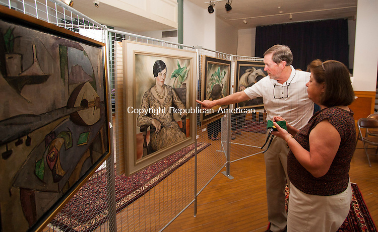 WOODBURY, CT - 09 APRIL 2015 - 050915JW11.jpg -- Chris and Christiane Wood of Woodbury look over the artwork of Natalie Van Vleck during the first showing of the artist's work outside Flanders Nature Center since 1992 during an exhibition sponsored by The Arts Alliance of Woodbury at the old Town Hall Saturday evening.  Jonathan Wilcox Republican-American