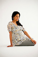 Pregnant Hispanic woman, sitting down