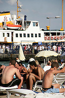 On the beach at Kinaliada, one of the Princes Islands, as a ferry unloads more holidaymakers, Istanbul, Turkey