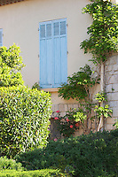 In a Provencal garden: a house with wooden window shutters painted pale blue and shrubs, bushes and flowers Clos des Iles Chambres d'Hotes Bed and Breakfast Le Brusc Six Fours Cote d'Azur Var France Clos des Iles Le Brusc Six Fours Cote d'Azur Var France
