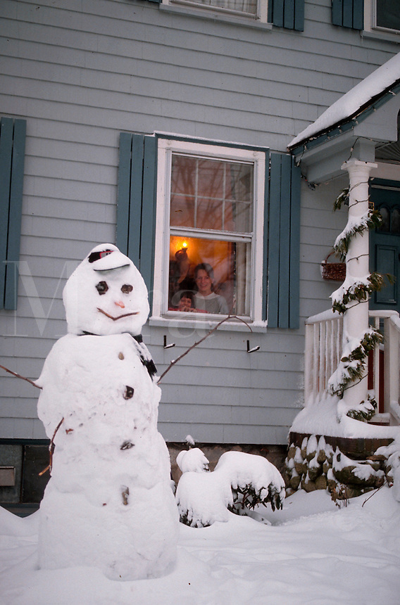 People in house looking out of window at a snowman.