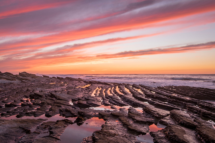 Water-filled furrows of rock strata reflect the dramatic sunset over the ragged shoreline at Montana de Oro state park.