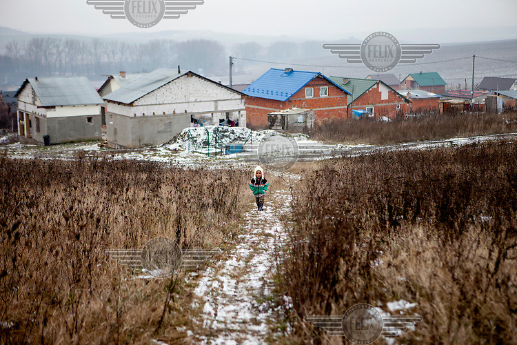 A young Roma girl walking near her family home which was built as part of a pilot project constructing low-cost houses called 'From Shack into a 3E (Ecological and Energy Efficient) House, which was implemented in the village of Rankovce in 2013. The pilot project took place in a marginalised Roma community - all the builders were<br /> unemployed Roma living with their families in difficult conditions.