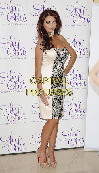 Amy Childs.Photocall to showcase her latest a/w 2012 fashion collection, The Millennium Hotel, Grosvenor Square, London, England..12th September 2012.full length white black lace strapless dress gold choker necklace diamante bracelet beige shoes peep toe hand on hip.CAP/CAN.©Can Nguyen/Capital Pictures.