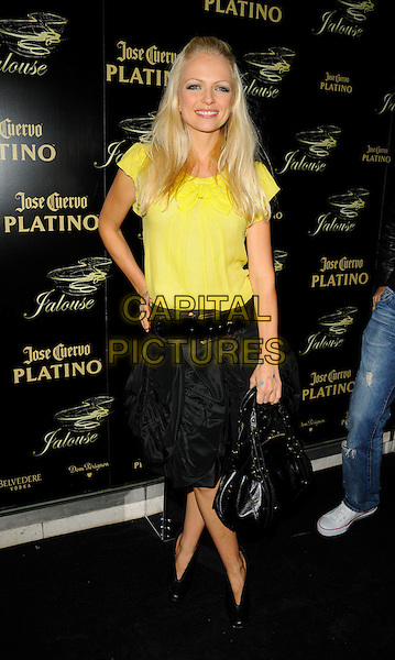 HANNAH SANDLING.The Jalouse club launch, Jalouse nightclub, Hanover Square, London, England..October 8th, 2008.full length black skirt bag purse ankle shoes boots yellow sheer top belt hand on hip.CAP/CAN.©Can Nguyen/Capital Pictures.