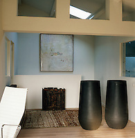 Skylights give added light to a dark corner of this living space. Two large stone urns stand near a brown pattern rug on a wooden floor.