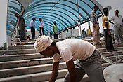 Construction workers are seen working on the metro station site of the Jawahar Lal Nehru stadium in New Delhi, India.