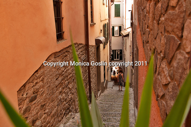 A woman walks down a cobble stone path in Bellagio, Italy a town on Lake Como