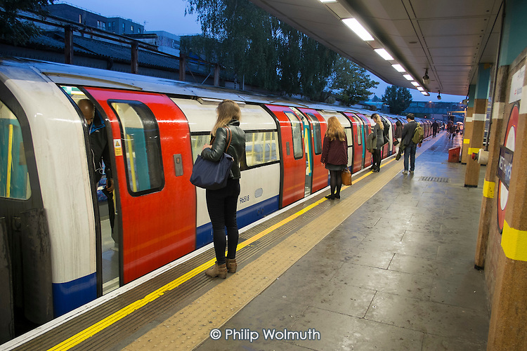 Passengers wait to board a tube train at a London Underground station