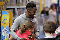 Pictured: A young girl hugs Nathan Dyer Wednesday 08 December 2016<br />Re: Swansea City FC players have bought Christmas gifts for 60 children at Smyths toy store in Swansea, south Wales.