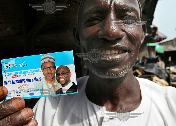 A voter holds a card bearing portraits of presidential candidate Major General Muhammadu Buhari and his running mate Pastor Tunde Bakare in Lagos. Nigerians turned out for a delayed parliamentary election on 9 April 2011 to make their choices on who represents them.