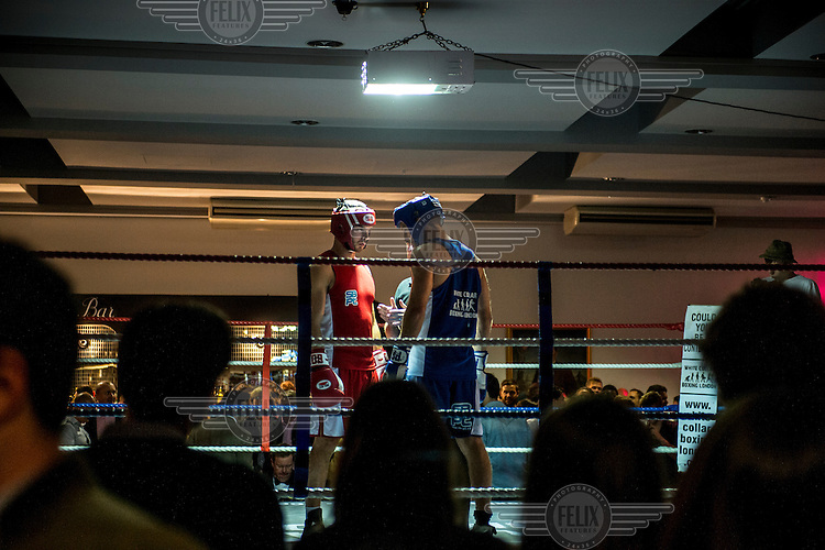 Will Judd (left) eyes up his opponent just before the beginning of the fight at a white collar boxing event at the London Irish Centre where the 'Carpe Diem' boxing event is taking place. <br /> <br /> 'White-collar boxing' is a growing phenomenon amongst well paid office workers and professionals and has seen particular growth in financial centres like London, Hong Kong and Shanghai. It started at a blue-collar gym in Brooklyn in 1988 with a bout between an attorney and an academic and has since spread all over the world. The sport is not regulated by any professional body in the United Kingdom and is therefore potentially dangerous, as was proven by the death of a 32-year-old white-collar boxer at an event in Nottingham in June 2014. The London Irish Centre, amongst other venues, hosts a regular bout called 'Carpe Diem'. At most bouts participants fight to win. Once boxers have completed a few bouts they can participate in 'title fights' where they compete for a replica 'belt'.