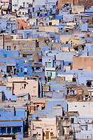 The village houses are clustered together, many exteriors painted the traditional blue of the region