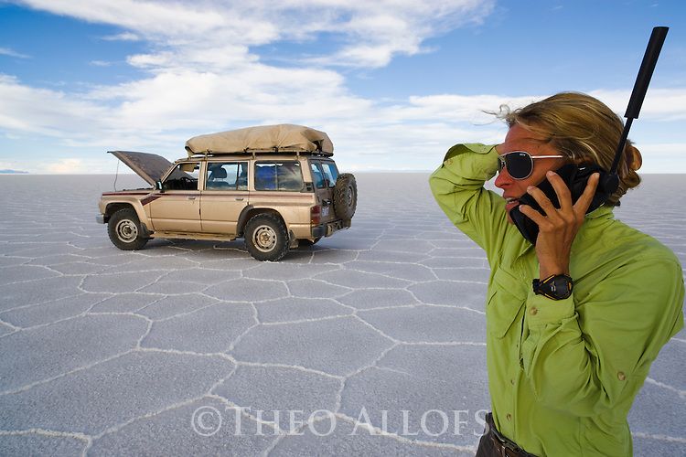 Bolivia, Altiplano, woman holding satellite phone  on Salar de Uyuni, world's largest salt pan; broken down 4x4 vehicle in background