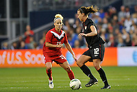 USWNT midfielder Lauren Cheney (12) facing up against Canada forward Kelly Parker.