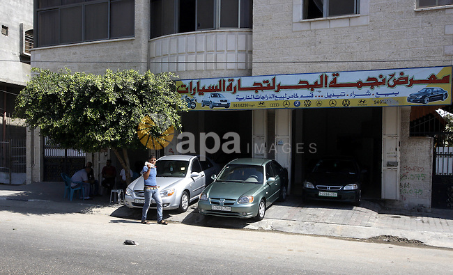 A Palestinian man walks near cars, at a showroom in Gaza City on Sep. 7, 2011.  while Israel stop to enter cars into Gaza Strip again after it allowed to enter them as a part of a new strategy to increase Gaza blockade. Photo by Mahmud Nassar
