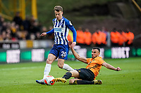 7th March 2020; Molineux Stadium, Wolverhampton, West Midlands, England; English Premier League, Wolverhampton Wanderers versus Brighton and Hove Albion; Romain Saïss of Wolverhampton Wanderers gets contact to clear the ball from the feet of Solly March of Brighton & Hove Albion